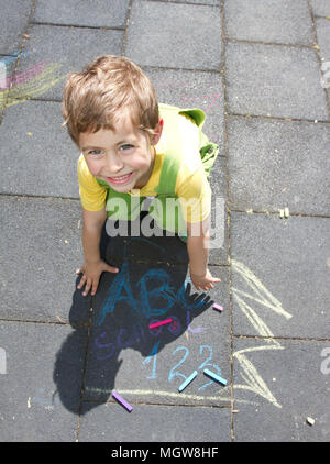 Cute boy write with colored chalks. Little kid draws with chalks. School, ABC and 123 sigh written with colored chalks. Vacation concept. Education. - Stock Photo