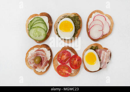 variants of sandwiches with cream cheese, pesto, tomatoes, cucumber, egg, bacon, radishes on a light background. view from above - Stock Photo