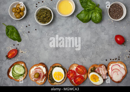 variants of sandwiches with cream cheese, pesto, tomatoes, cucumber, egg, bacon, radishes on a gray background. view from above - Stock Photo