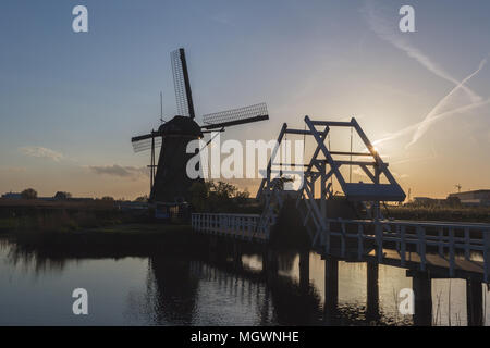 Sunset on windmill reflected in the canal Kinderdijk Molenwaard South Holland The Netherlands Europe - Stock Photo