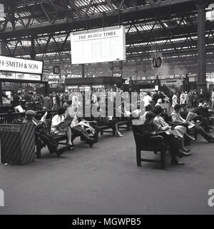 1950s, historical, rail passengers at St Pancras railway station sit on benches reading newspapers while awaiting their trains, London, England, UK. As can be seen in distance, it was very much still the era of steam, which can be seen arising from the platforms. The station was built by Midland Railway as their own central London terminus and opened in 1868, with its famous single-structure roof or trainshed designed by William Henry Barlow. - Stock Photo