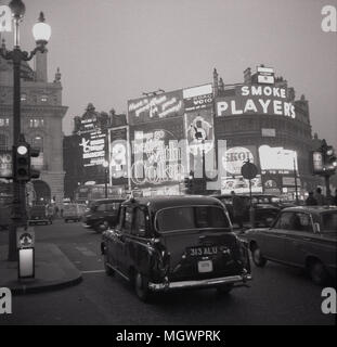 1960s, historical picture of a London taxi and a car waiting at the traffic lights at the busy roundabout, Piccadilly Circus, London, England, UK. The famous billboards with advertising for brands such as 'Players' cigarettes and Coke can be seen. - Stock Photo