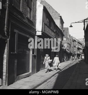 1950s, historical picture of 'The Shambles' in York, England, UK, an old medieval narrow cobbled street lined with overhanging ancient timber-framed buildings and famous for the butcher shops (25 in 1872) that used to trade along it in the 19th century. Indeed the word 'shambles' is an old term for slaughterhouse. - Stock Photo