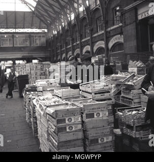 1950s, historical picture, two market traders make notes of their sales, surrounded by their crates of fruit inside the hall area at Covent Garden's famous fruit and vegetable market, London, England, UK. - Stock Photo