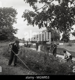 1950s, historical, adult female volunteers working on flower or raised bed verges at a canal lock, England, UK. - Stock Photo
