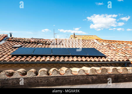 Solar panels on tiled roof of a house in a small Languedoc village in southern France. - Stock Photo