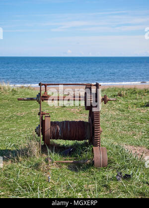 An Old rusting Manual Boat Winch used for hauling in Fishing Boats lies abandoned on the Grassy Bank behind the Beach, in Easthaven, Scotland. - Stock Photo