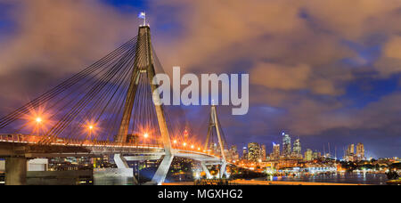 Anzac bridge with flags of Australia and New zeland on top gates with steel cables in front of Sydney city CBD urban towers at sunset with bright illu - Stock Photo