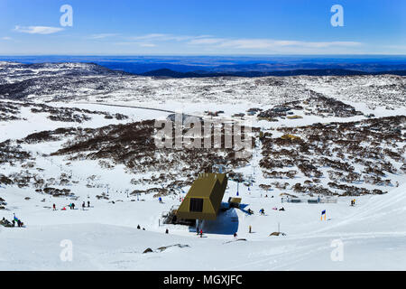 From the top of Back perisher mountain in snowy mountains looking down at ski resort infrastructure and chair lift with skiers and snowboarders above  - Stock Photo