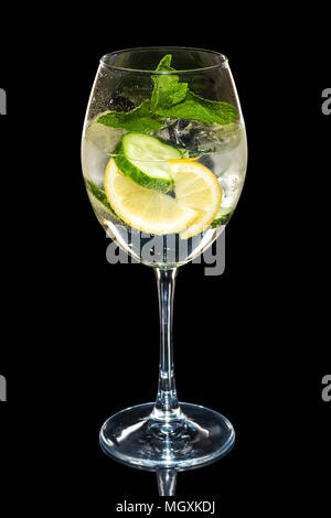 Cold Lemon and cucumber cocktail with a sparkling wine with ice cubes in wine glass isolated on black - Stock Photo