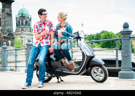 Scooter riding tourists drinking coffee in Berlin - Stock Photo