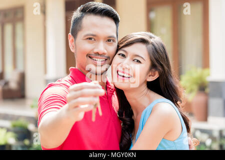 Portrait of young happy couple posing with the keys of a new house - Stock Photo