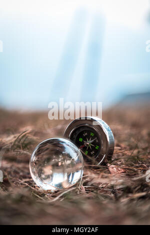 A mini compass and a crystal ball arranged on ground in the tiny Himalayan village of Lagga, located in Chamba - Stock Photo