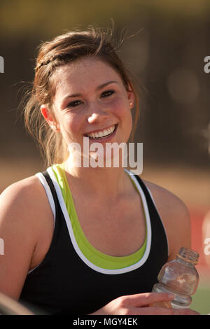Female high school tennis player smiles during match - Stock Photo