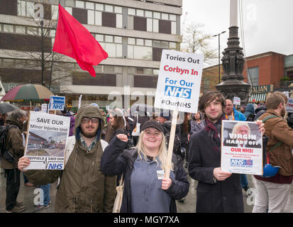 Demonstrators holding placards in at Sheffield Save our NHS protest rally, with red flag being waved in background - Stock Photo