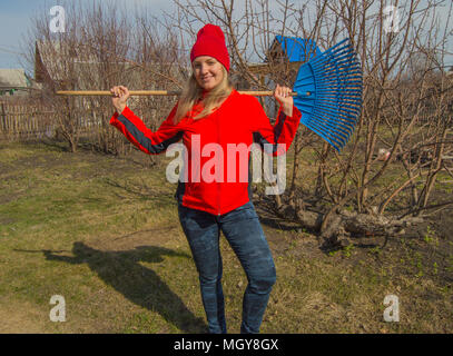 full length portrait of a smiling woman professional gardener with a rake, a beautiful blonde working in the garden - Stock Photo