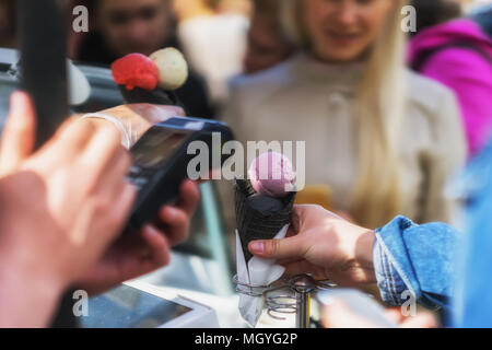 Queue for a variety of types of Delicious fresh ice cream with a new taste in black wafer horns. Payment via terminal by credit card. Real scene in th - Stock Photo