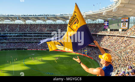 A West Coast Eagles fan waves the club flag after the team scores a goal in the Western derby at Optus Stadium, Perth, WA, Australia. - Stock Photo