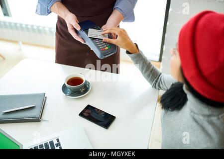 Young Woman Paying via NFC in Cafe - Stock Photo