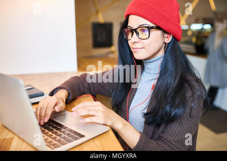 Trendy Woman Blogging in Cafe