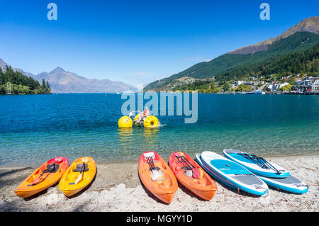 lake wakatipu from the lakeside with kayaks and water bicycles for hire and for rent rental kayaks lakeside queenstown South Island New Zealand - Stock Photo