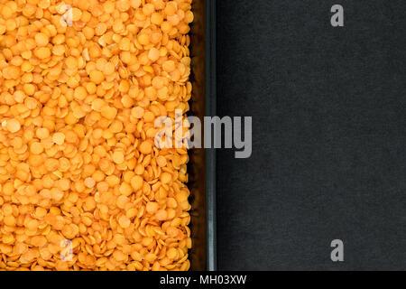 Red lentil grains in black plate on black stone background surface with free space splitted in half - Stock Photo