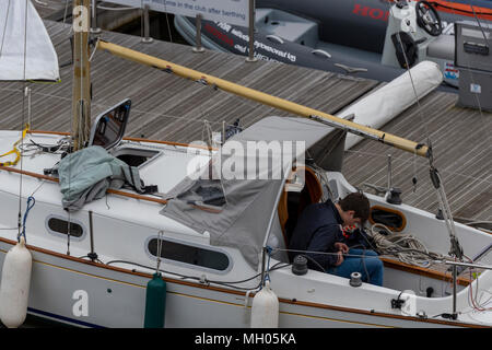 A young man or boy on a small sailing yacht learning the ropes at a young age.children or youngsters learning to sale a yacht sitting in the cockpit. - Stock Photo