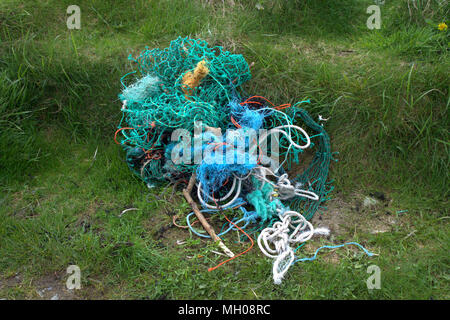 old trawl nets and nylon rope discarded on the grass verge. - Stock Photo