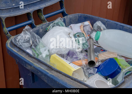 Close-up image on an opened blue plastic recycle bin used for household recyclable materials. Common, discarded household packaging are seen within. - Stock Photo