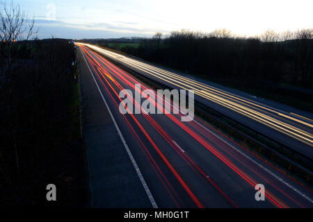 White headlights and red tail-lights on motorway at night in motion - Stock Photo