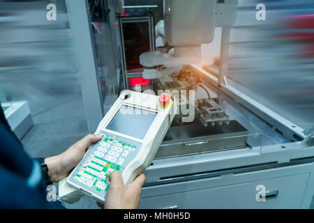 engineer using tablet to control machine in real time.Smart factory use Automation robot arm in automotive manufacturing - Stock Photo