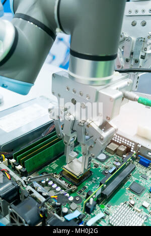 Robotic arm installing a computer chip - Stock Photo