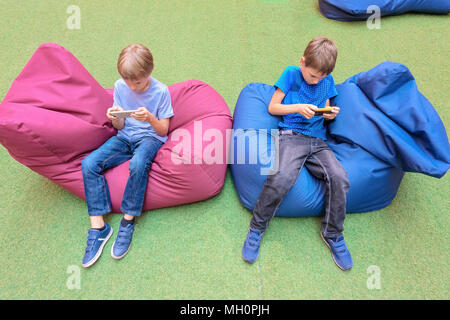 Children using mobile phone sitting on bag chairs - Stock Photo