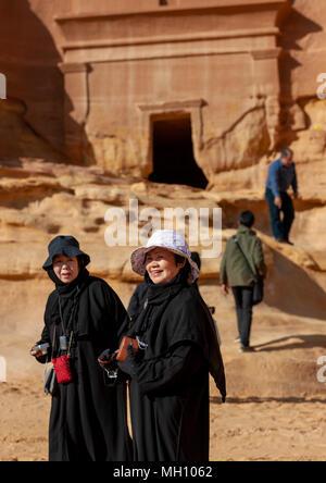 Tourists in madain saleh archaeologic site, Al Madinah Province, Al-Ula, Saudi Arabia - Stock Photo