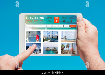 Man holding a tablet device visiting a travel company website and touching the screen with a finger with blue sky in background. - Stock Photo