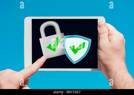 Man holding a tablet device pointing at an anti-spam, security firewall icon and touching the screen with a finger with blue sky in background. - Stock Photo