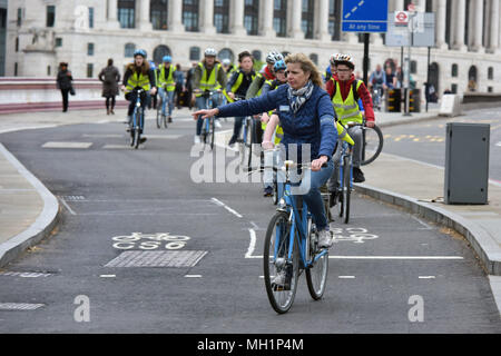 A Royal Parks official tour guide leads a pack of young tourists on London Bike Company bikes heading south on Blackfrairs Bridge in central London du - Stock Photo