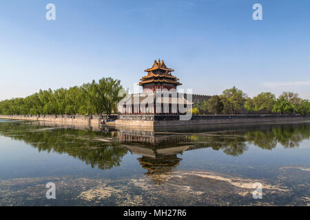 North East corner tower of the Forbidden City in Beijing, China. Two men in a small boat can be seen on the moat that surrounds the city walls. - Stock Photo