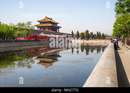 A group of friends catching fish in the moat surrounding the Forbidden City, Beijing, China. In the distance the Northern gate and crowds of tourists.