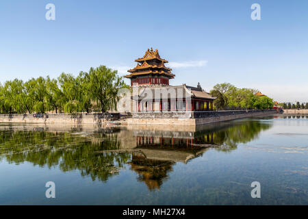 North East corner tower of the Forbidden City, Beijing, China. A reflection of the tower and willow trees can be seen in the moat surrounding the city. - Stock Photo