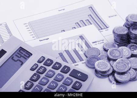 A calculator sitting on some graphs labelled savings and funds with some new (post 2016) pound coins. Stock Photo