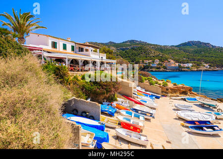 Fishing boats on shore in front of coastal restaurant in Sant Elm village, Majorca island, Spain - Stock Photo