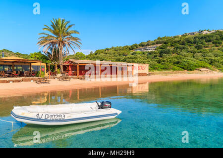 CORSICA ISLAND, FRANCE - JUN 23, 2015: Dinghy boat anchoring in small bay with beach and restaurant on sunny summer day. This French island is popular - Stock Photo