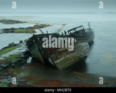 Abandoned derelict fishing boats on the south east coast of Mull, Scotland - Stock Photo
