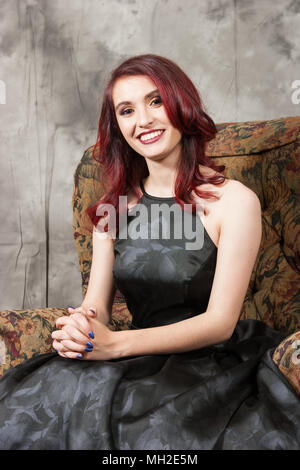 Pretty young redhead in black prom dress on floral pattern chair - Stock Photo