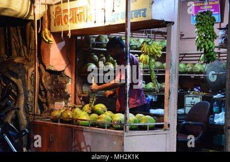 A man selling coconuts on his market stall in Margao, near Benaulim, Goa, India - Stock Photo