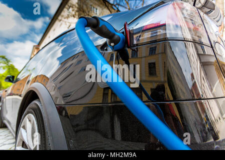Close up of the power supply plugged into an electric car being charged - Stock Photo