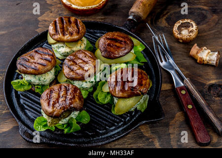 Grilled portobello bun mushroom burgers on cast iron grill pan ob wooden background, top view. - Stock Photo