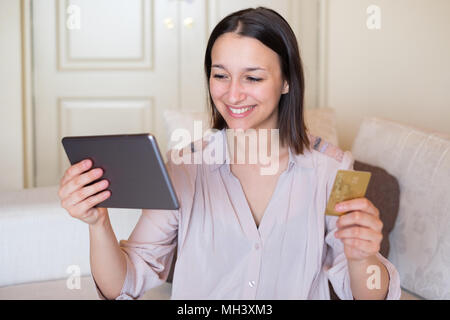 Happy young woman ordering and paying using credit card on online store - Stock Photo