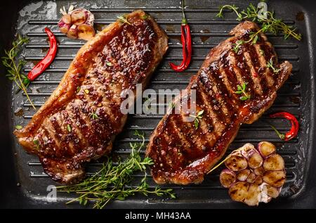Sliced steak Ribeye   Hamburgers on barbeque grill - Stock Photo